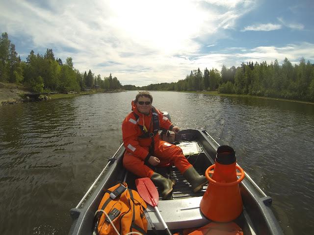 Pelastautumispukuinen henkilö ohjaa työvälineitä täyteen lastattua pikkuvenettä