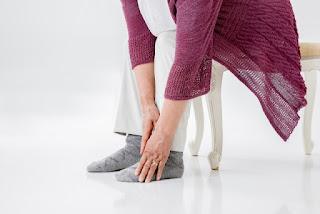 足先が冷たいので、手で温めている女性