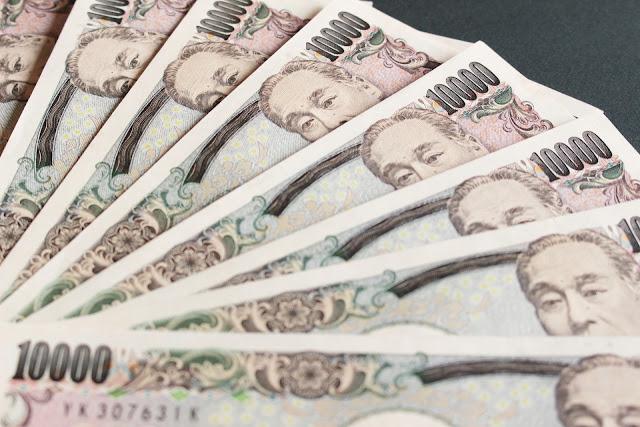 一万円札が何枚も重なっている