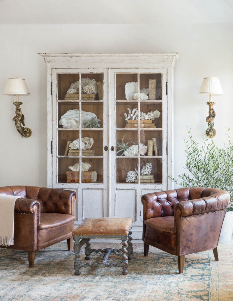 Leather club chairs and Swedish antique cabinet with glass doors by Giannetti