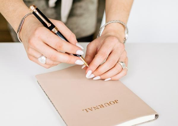 Mãos femininas segurando uma caneta acima de uma agenda