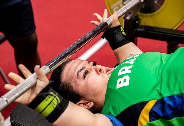 Mariana D'Andrea, atleta do halterofilismo paralímpico, se prepara para mais uma tentativa de erguer o peso. Ela está segurando a barra, antes do levantamento.