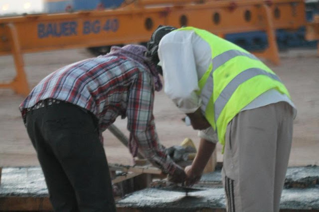 Picture of two workers working with concrete on the Kingdom Tower construction site