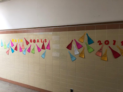 Ms. Blaser printed her students' matholution pennants on colored paper and displayed them on the wall in the hall.