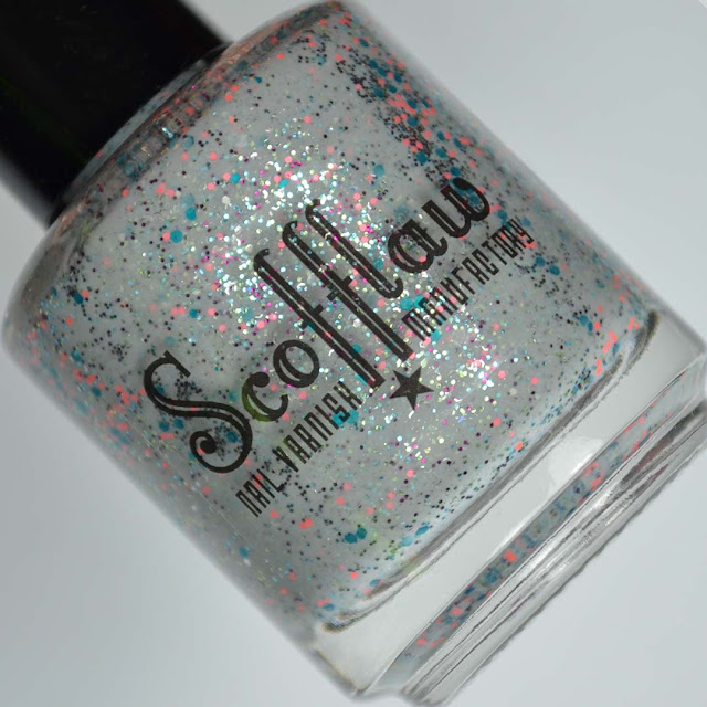 grey nail polish with pink and blue glitter in a bottle