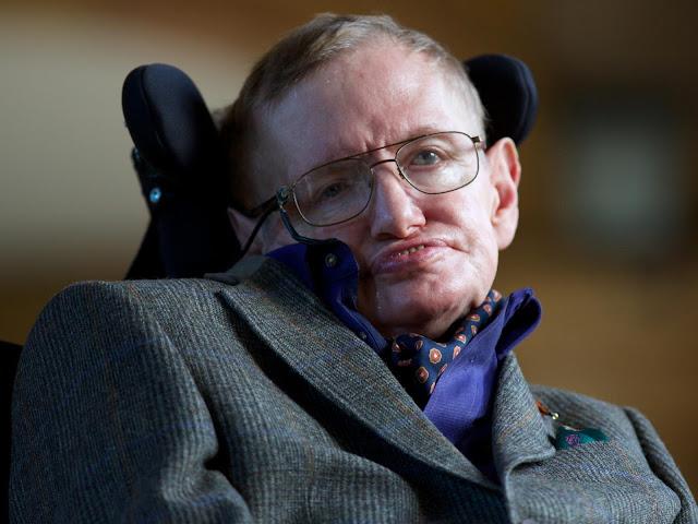 A imagem mostra Stephen Hawking em sua cadeira de rodas motorizada.