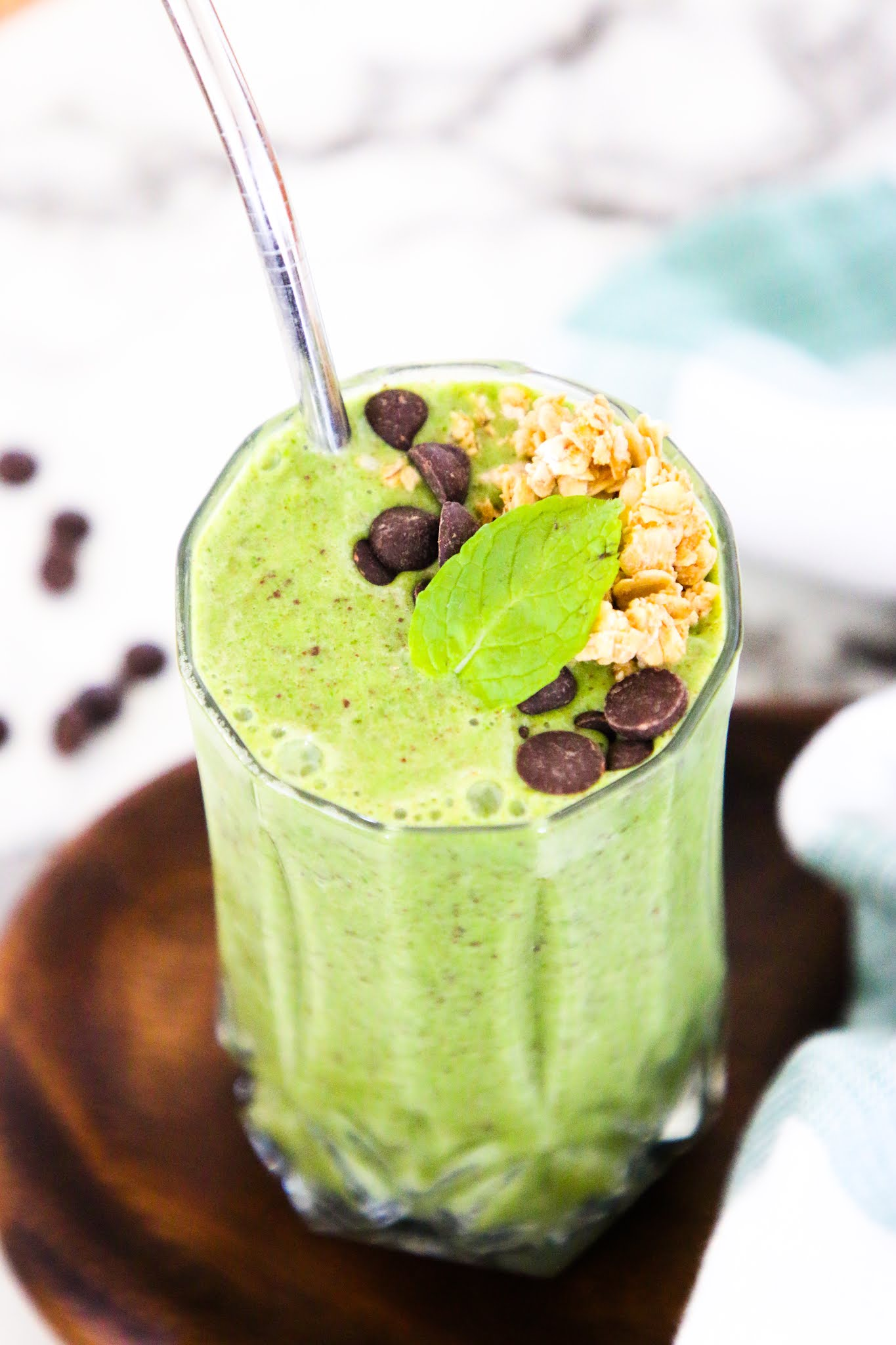 Health shamrock shake smoothie on a marble table top with a metal straw.