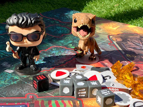 Tyrannosaurus and Dr Malcolm figures on playing board