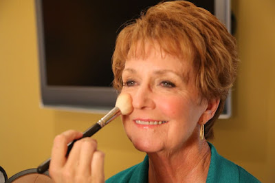 senior woman applying makeup