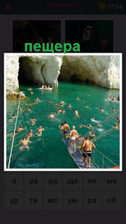 вход в пещеру и рядом с мостика ныряют люди в воду