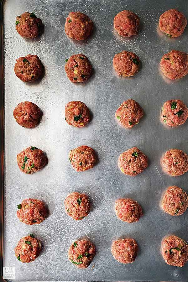 Overhead view of Mediterranean meatballs on a baking tray ready for the oven