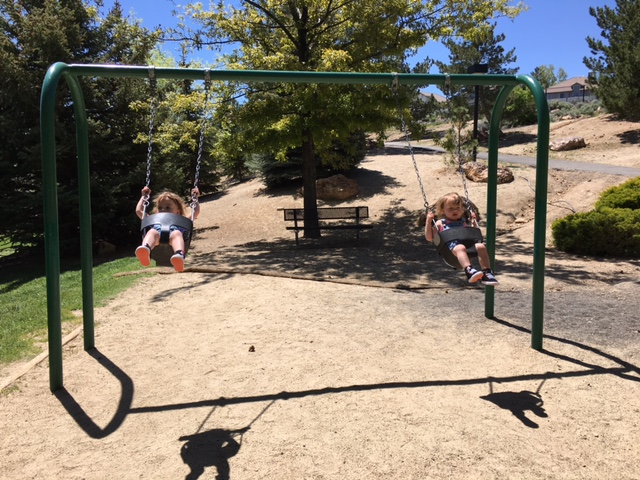 toddlers swinging at the park