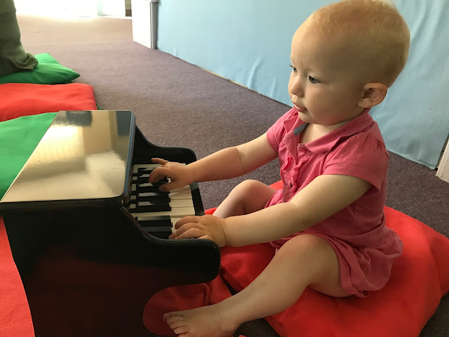 A 1 year old in a pink dress sitting on a red pillow and playing a small black piano