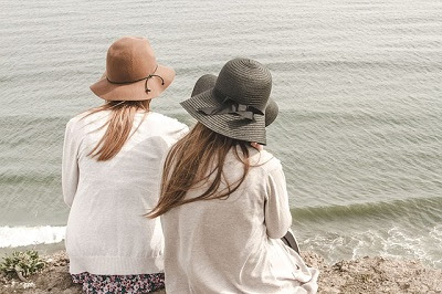 2 Women Sitting on the Sand at the Beach Looking at the Waves