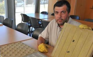 Imagen de Gustavo Maenza- creador del proyecto- con una de las baldosas con atracción magnética.