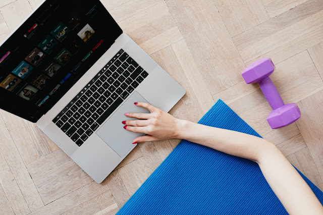 A girl led on a yoga mat next to her laptop looking for workout videos online