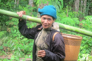Local Bunong woman carrying bamboo