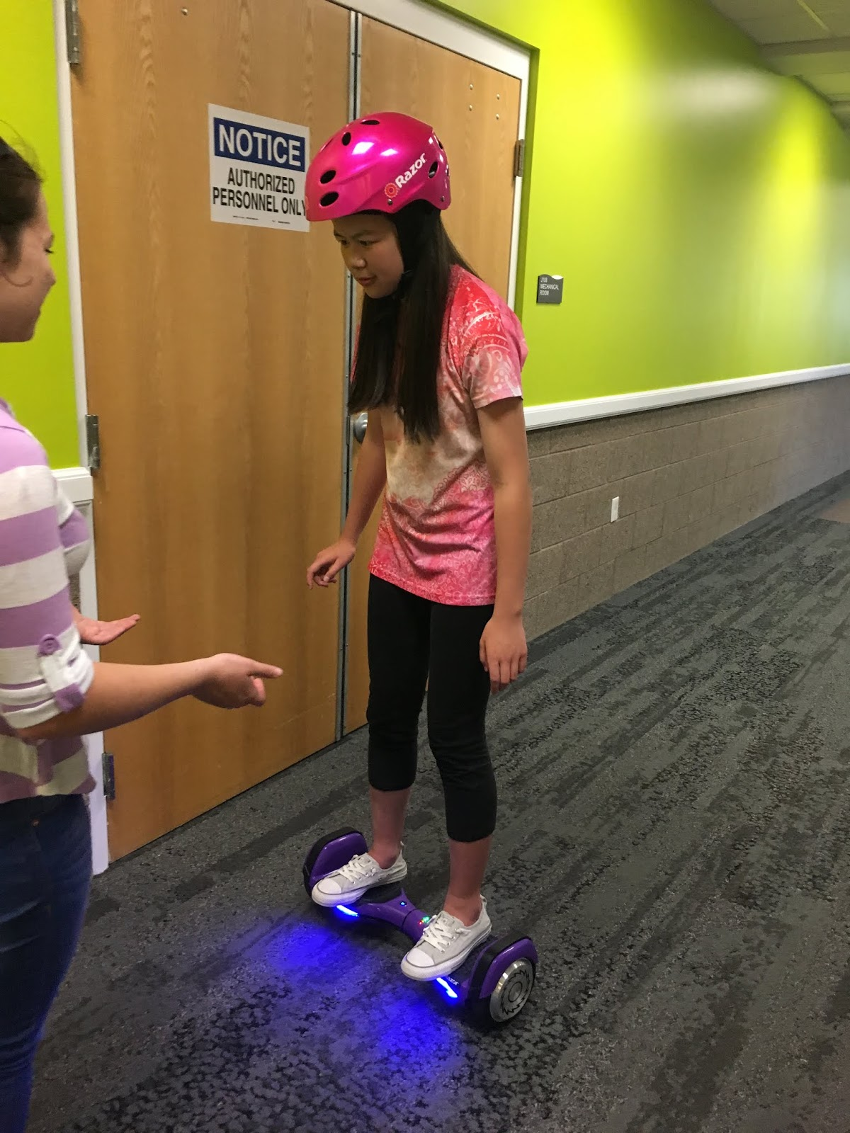 a female student moves forward on a hoverboard