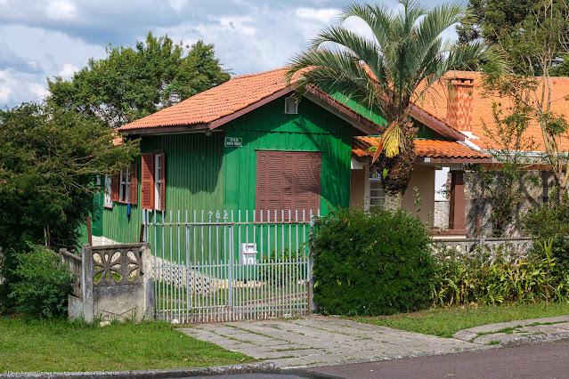 Vista de perfil de simpática casa de madeira no Bacacheri