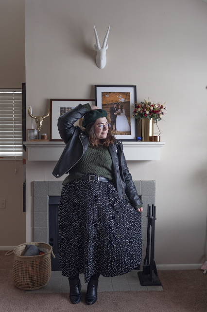 An outfit consisting of a dark green beret, black moto jacket, green sweater tucked into a black and white dotted midi skirt and black chelsea boots.