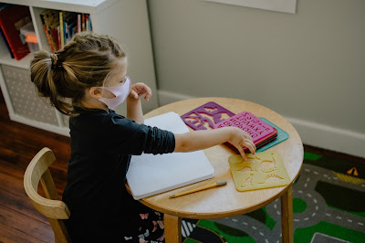 little girl with mask on sitting at table with books