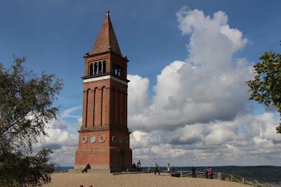 man sieht einen Turm aus rotem Backstein, der im Himmel zu schweben scheint