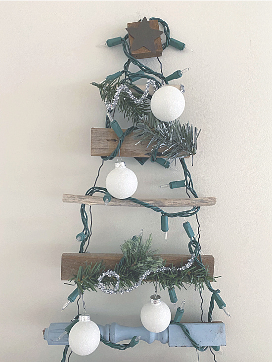 ornaments and greens on a scrap wood tree