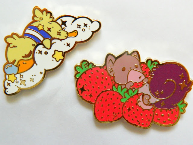 A photo showing two pin badges: one of a sleeping duck on a cloud and one of a squirrel surrounded by strawberries