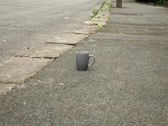 Grey mug abandoned on tarmac pavement with wide stone edging.