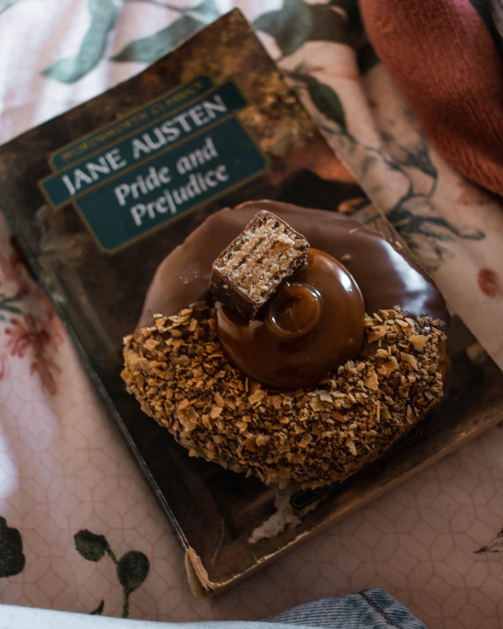 chocolate donut sitting on top of a book of pride and prejudice by jane asten