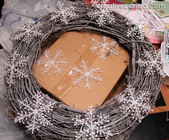 glueing dollar store snowflakes to a grapevine wreath