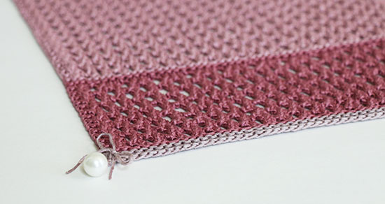 Close up of a pearl bead tied to the corner of a hand knit pink linen table runner on a white background.
