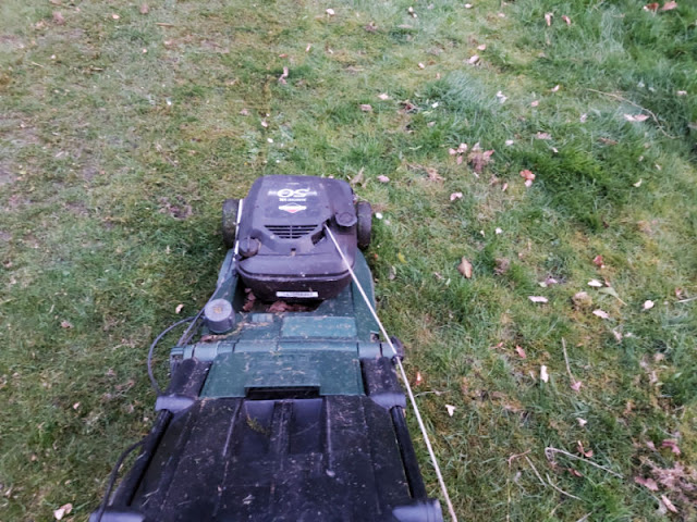 A lawnmower on the grass: to the left, the grass has been cut, to the right it is still long