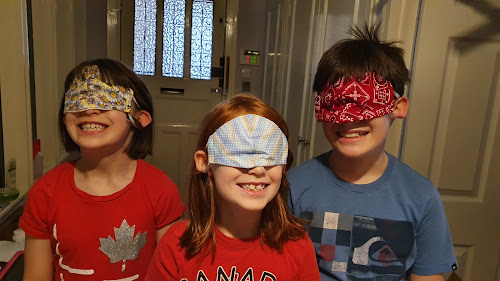 Three kids, wearing masks over their eyes, grin like fools.