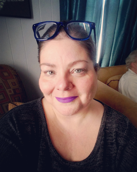 image of me from mid-chest up; my hair is pulled up, my blue-framed glasses are on my head, and I'm wearing purple lipstick as I smile at the camera