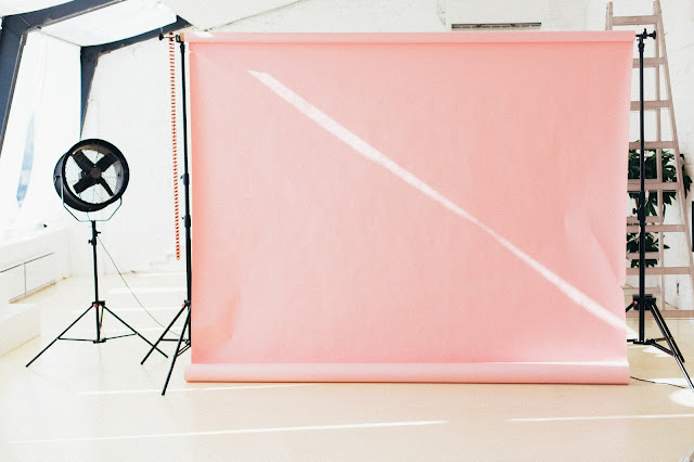 A photography studio featuring a peach backdrop.