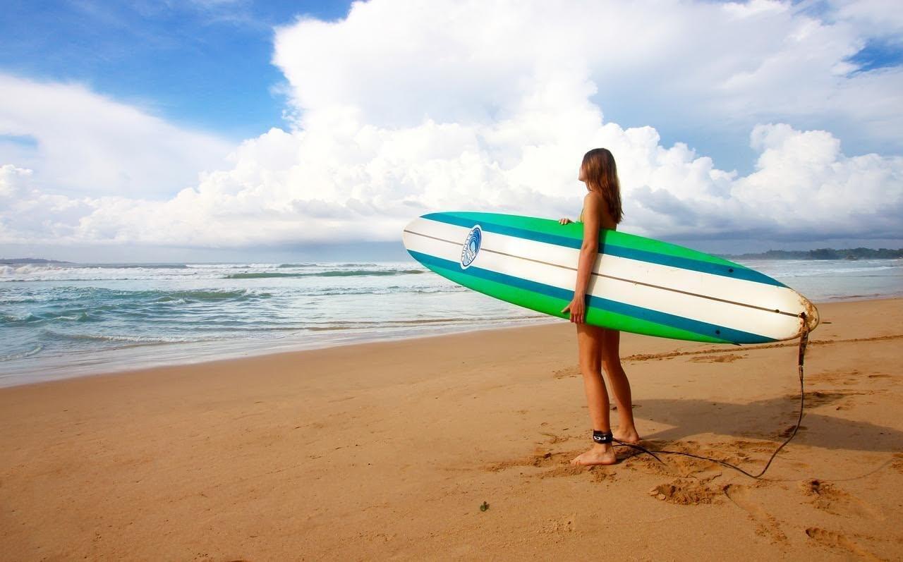 女の子がビーチでソフトボードを抱えて海に入って行こうとしている写真