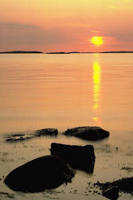 Nascer do sol no mar, praia com pedras. #PraCegoVer