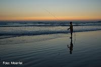Foto de um pescador pescando na praia ao amanhecer