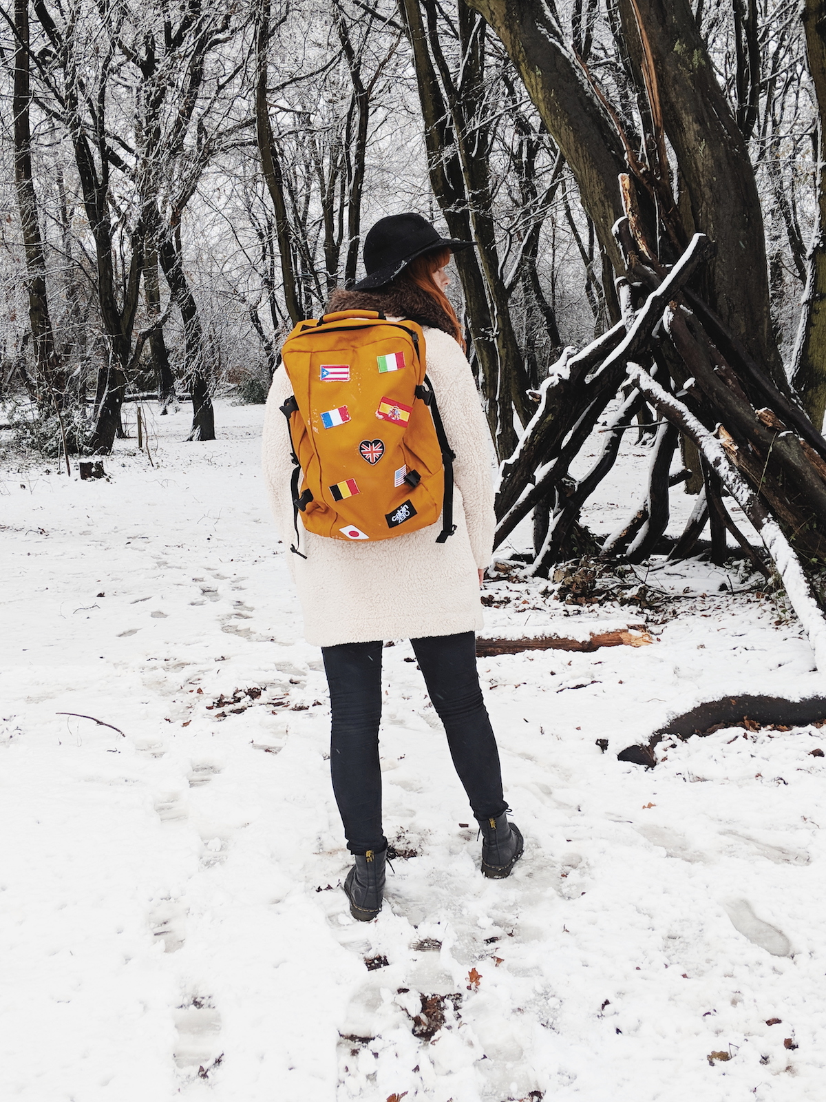Travel blogger, Leigh Travers, walks amongst a snowy forest scene with her Cabin Zero rucksack. View of the bag worn face-on.