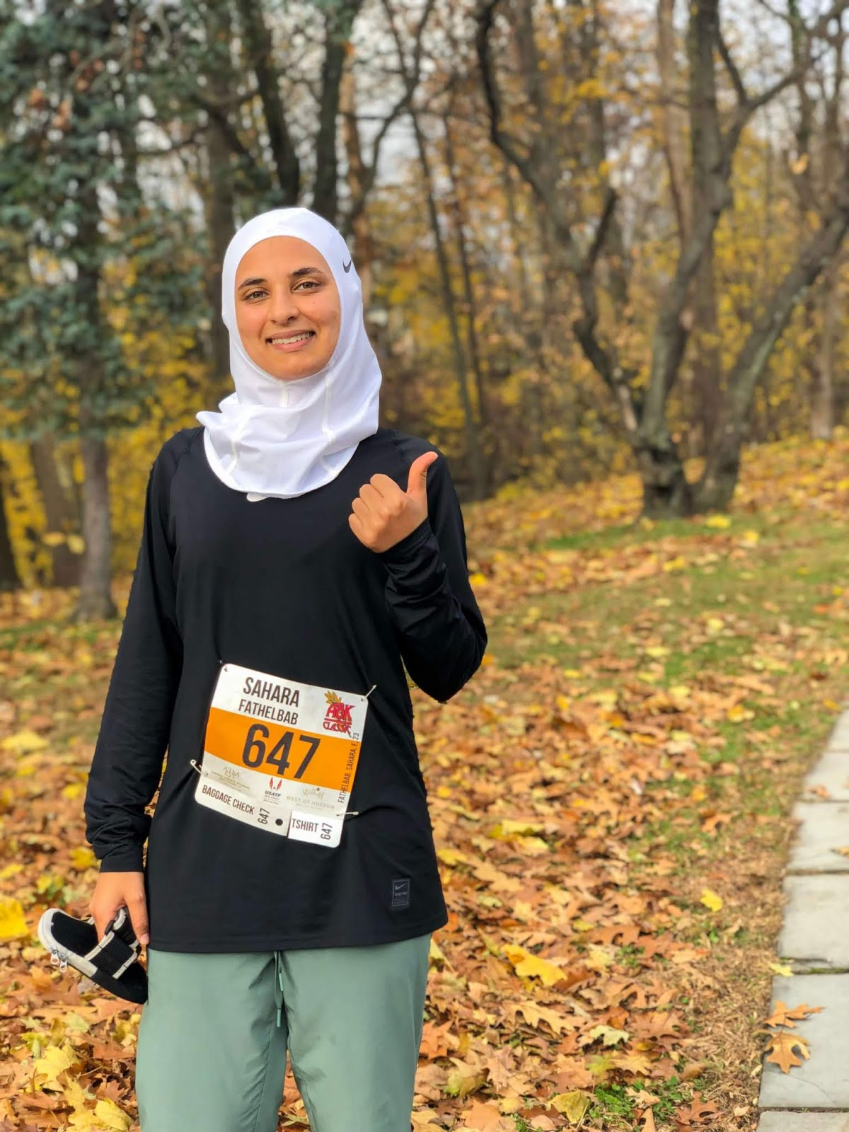 sahara after 8K race - thumbs up standing in front of trees and leaves
