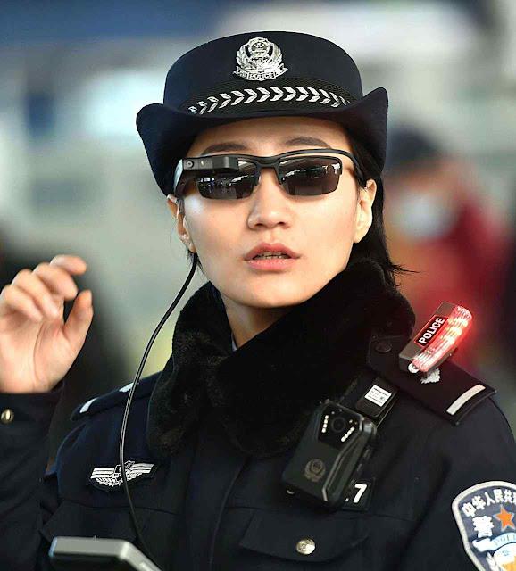 Policial com óculos de reconhecimento facial na estação ferroviária de Zhengzhou.