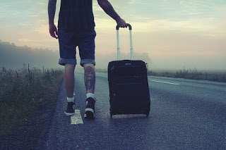 Man wheeling a suitcase