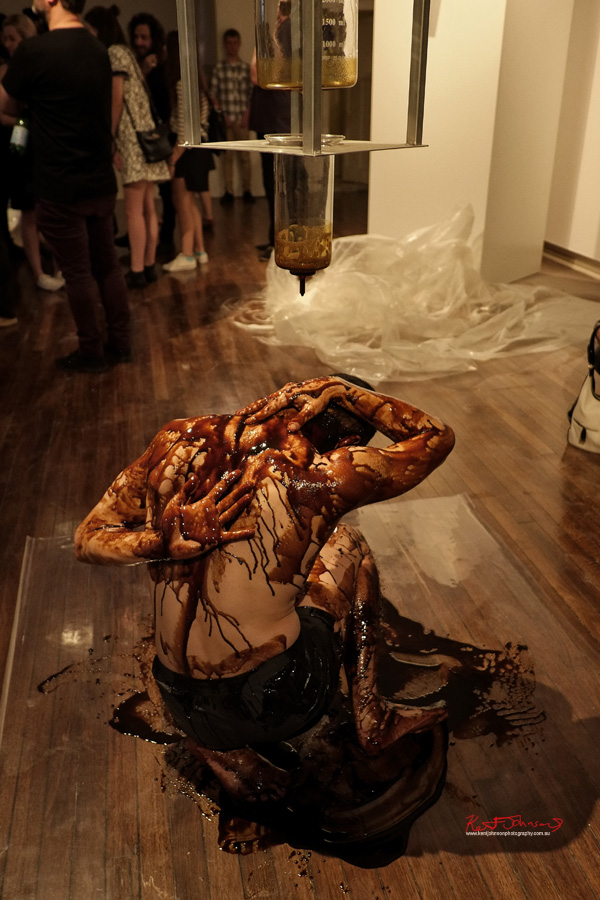 Live performance piece - Contorted male body being dripped with Dark StickySyrup - Madeline Beckett's Press Her at KUDOS Gallery. Photography by Kent Johnson for Street Fashion Sydney.