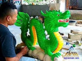 Patung naga dibuat dari batu alam putih yang di cat hijau