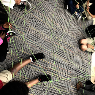 Students create a web with yarn, each connection depicts positive statements made to peers.