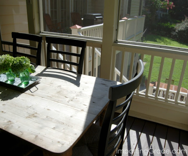 From screened porch dining area, you can see adjacent deck and patio below