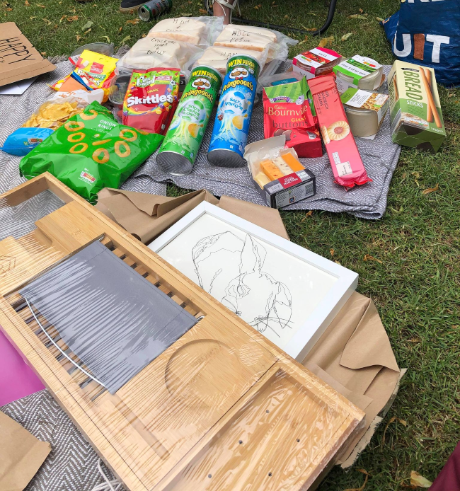 Picnic snacks and presents on a blanket on the grass