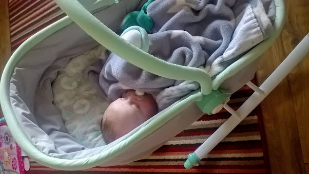Image of a baby laid sleeping in the East Coast Rocker covered in a blanket and suckling on a mam dummy/pacifier