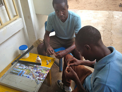 Nortey Quaynor and another student, operating a large paper slicer to make paper beads.